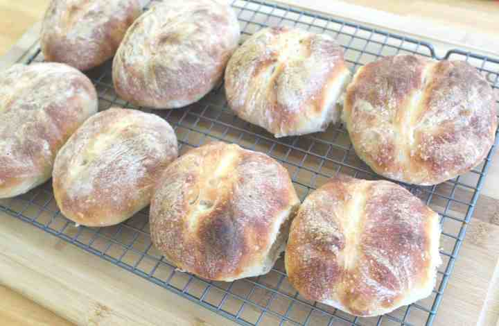 8 freshly baked breads in the cooling rack. They look uneven but with a beautiful baked crust.