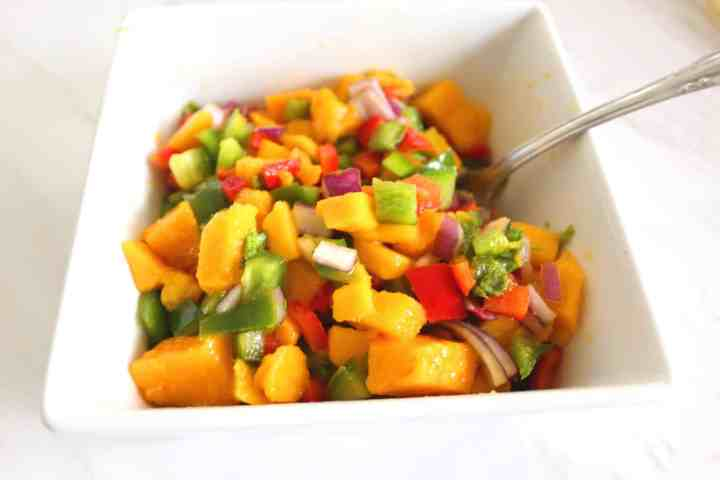 A square bowl with mango salsa that has a spoon in it.