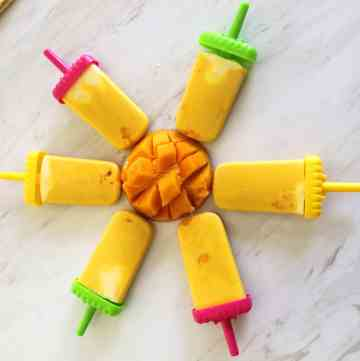 Mango popsicles in a circular shape with a cut mango in the middle