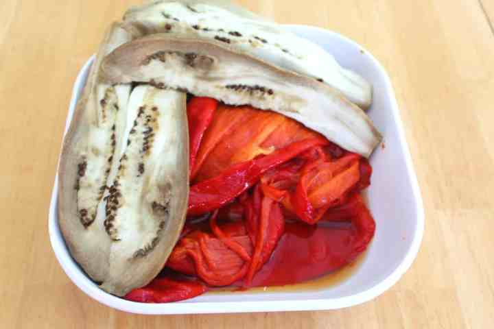 Peeled red peppers and eggplant on a plate.