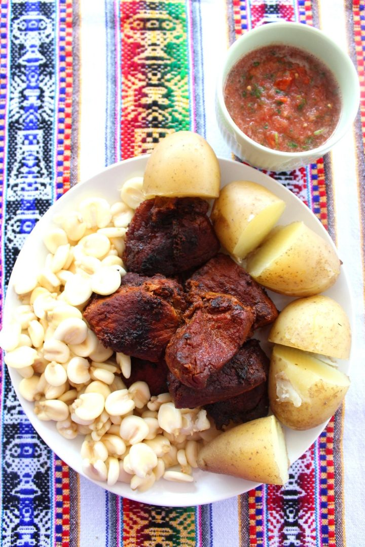 Pork chicharron served on a platter with mote (white large grain corn) and boiled potatoes. Next to the platter, there's a serving of a llajua (a Bolivian tomato salsa).