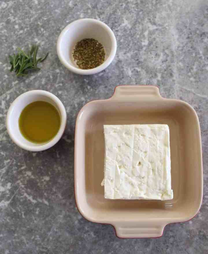 Ingredients for baked feta cheese - feta cheese block in a baking tray, fresh rosemary, dry oregano and olive oil.