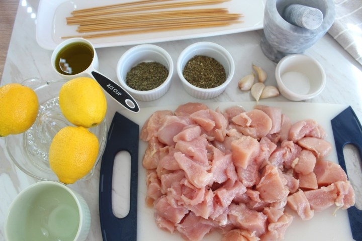 All the ingredients together on a flat surface for the chicken kabobs. You see herbs, lemons, cut chicken, a mortar and pestle, oil and skewers in water.