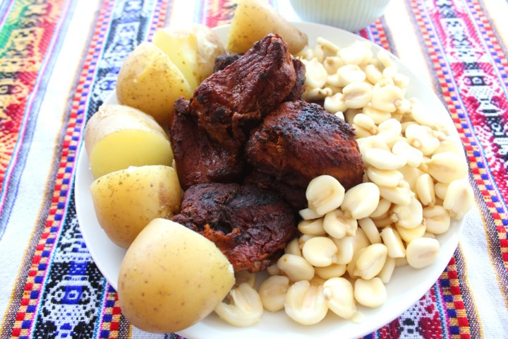 Pork chicharron served with mote and potatoes on a platter. Plate is over a tablecloth with patterns.