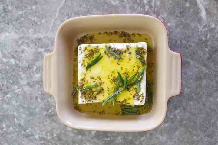A square baking dish with a block of feta cheese, covered in olive oil and herbs.