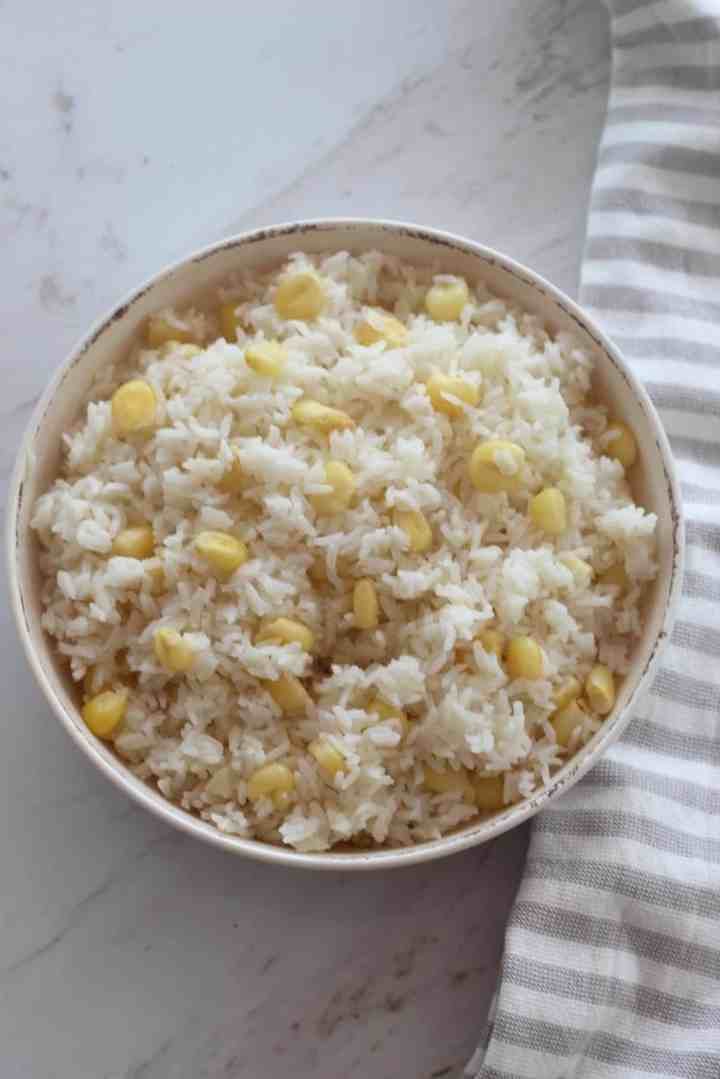 A round dish with fluffy rice and big kernel corn called choclo.