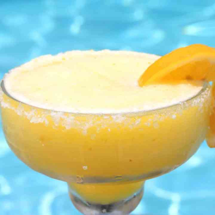 A frozen margarita drink next to a pool. Cup has a salty rim and the outside of the cup shows condensation.