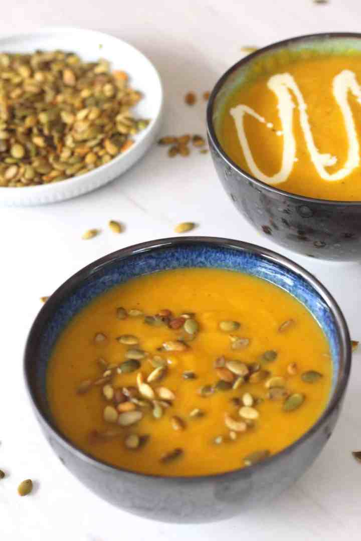 A bowl of soup forefront shown with a creamy Fall soup. Soup is topped with pumpkin seeds. There's another bowl of soup in the background that is topped with cream.