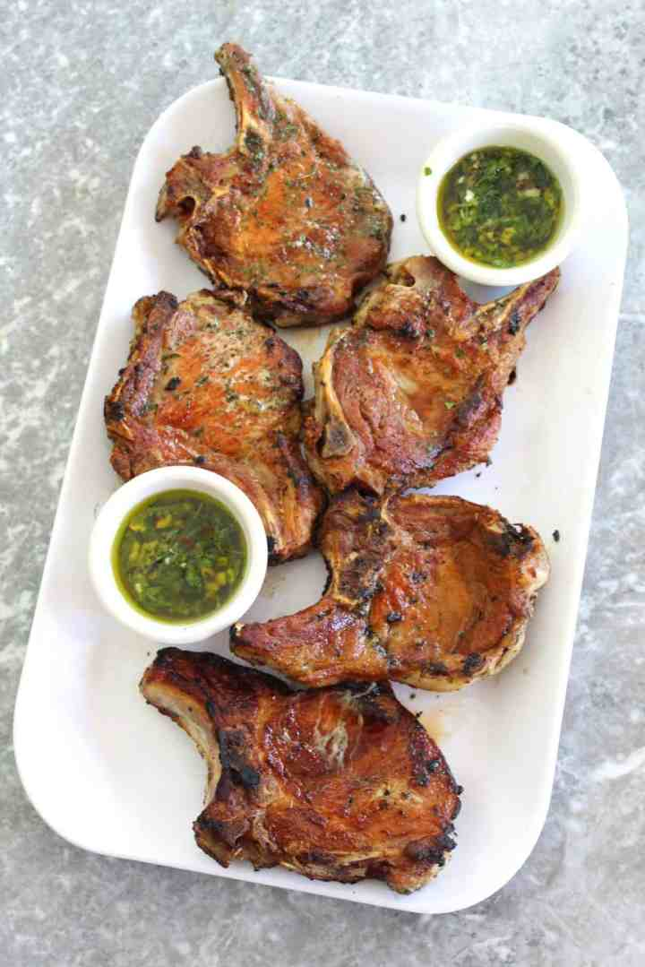 A platter with 5 golden brown, juicy pork chops served with an oily herbed sauce (mint chimichurri).