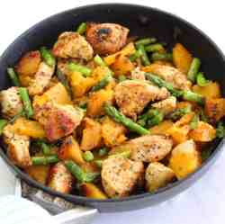 A skillet with chicken, butternut squash and asparagus