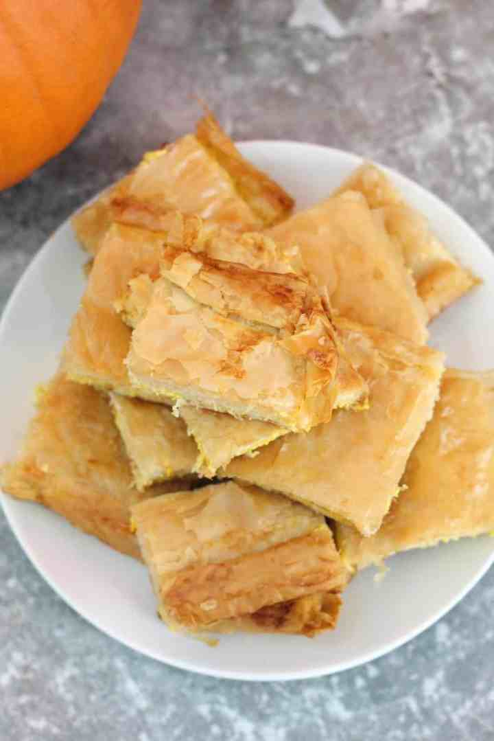 A plate full of slices of byrek, a phyllo pumpkin pie. In the background you can see a little bit of a pumpkin.