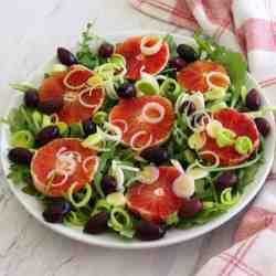 A salad platter with greens, blood orange, olives and leeks.