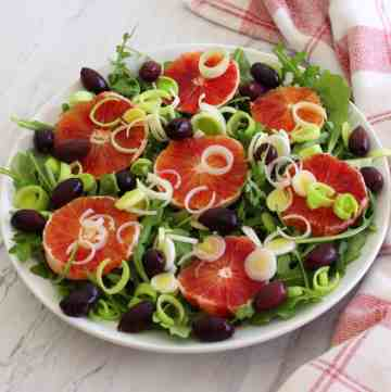A salad platter with greens, blood orange, olives and leeks.