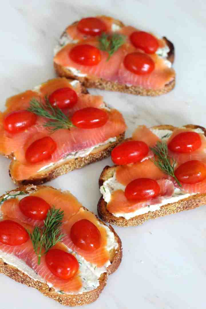 Ricotta crostini topped with smoked salmon, cherry tomatoes, dill and olive oil. This picture shows 4 crostini at different angles