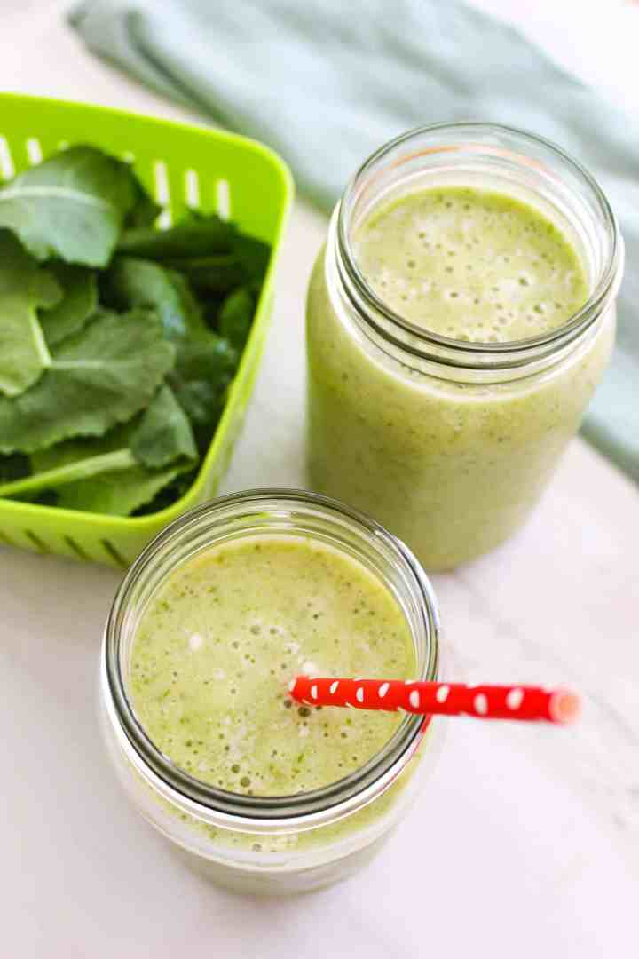 Two jars of green smoothie next to fresh kale.