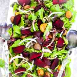 A rectangular salad dish with greens, beets, and chestnuts