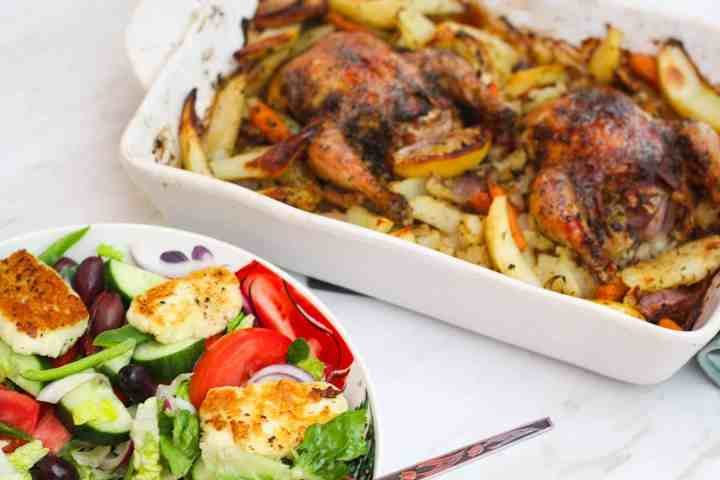 Halloumi salad served next to a bakes dish with Cornish hens and potatoes.