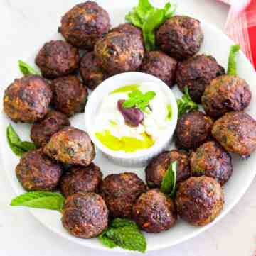 Qofte - mint meatballs in a platter, garnished with mint and yogurt dip.