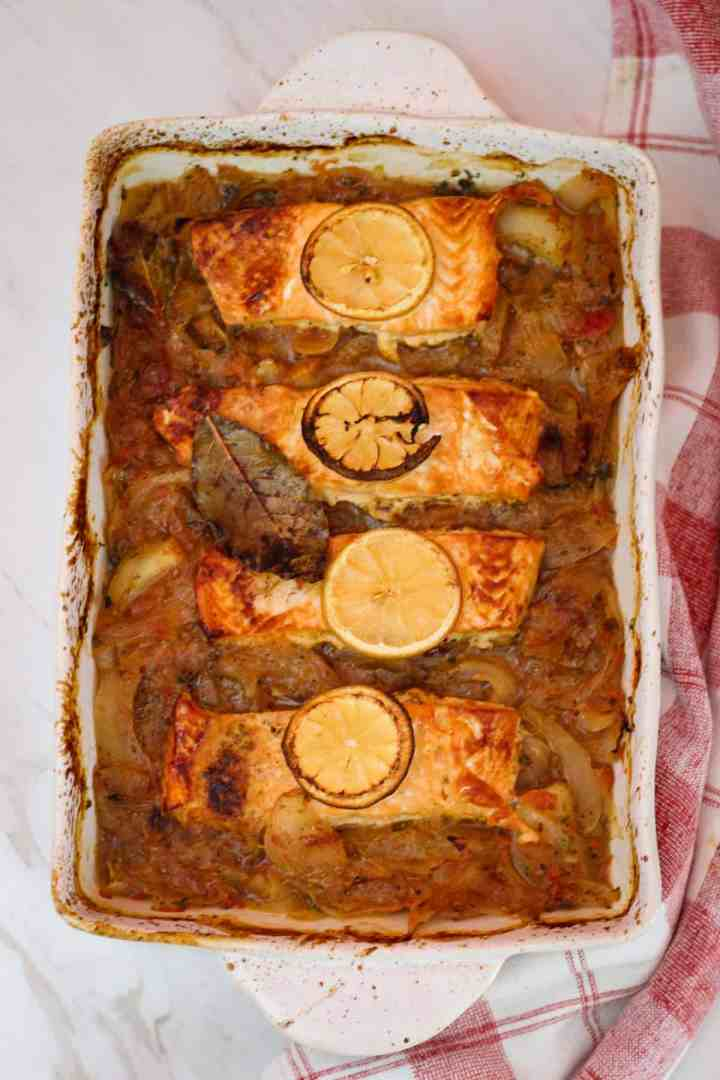 A rectangle baking dish with salmon, onions and lemon. Dish is already baked.