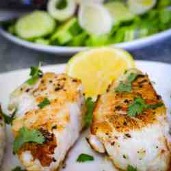 Seared Chilean sea bass on a platter, garnished with cilantro and lemon slices. In the background you see a salad platter.