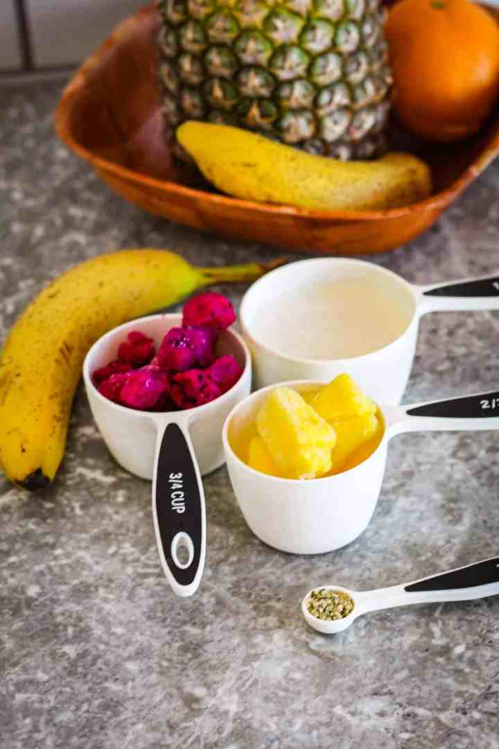 Ingredients for smoothie: dragon fruit, pineapple, banana, oat milk and hemp hearts seeds. Ingredients are shown next to a basket of fresh fruit.