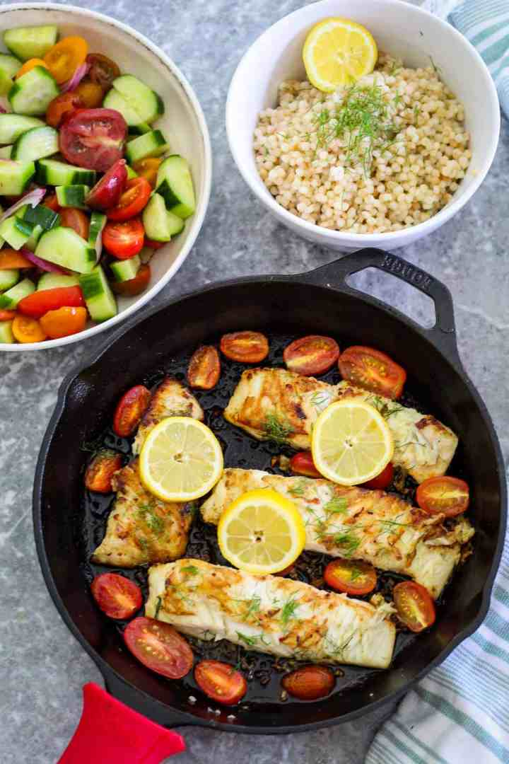 Halibut fillets in a cast iron skillet, shown with cherry tomatoes and lemon. There's a salad and couscous dish on the side as side dishes.