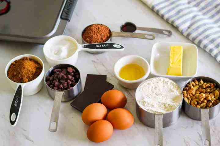 Ingredients for making triple chocolate brownies with walnuts: sugar, brown coconut sugar, cocoa, vanilla, avocado oil, butter, chocolate chips, chocolate bars, eggs, AP flour, chopped walnuts.