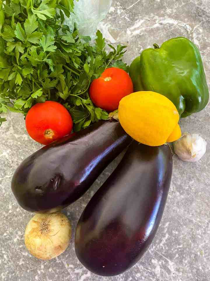 Fresh ingredients used to make the relish: eggplants, bell pepper, tomatoes, parsley, lemon, onion and garlic. Other ingredients like olive oil or seasonings are not shown in the picture.