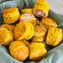 Pumpkin biscuits on a serving basket lined with a green napkin.