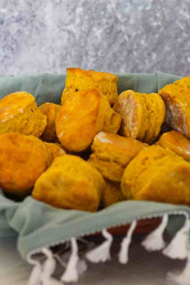 Basket of homemade pumpkin biscuits. Biscuits are over a green napkin.