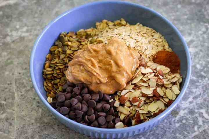 A blue bowl full of ingredients, not mixed yet. You can see on a circular shape oats, almonds, chocolate chips, cinnamon, pumpkin seeds and peanut butter.