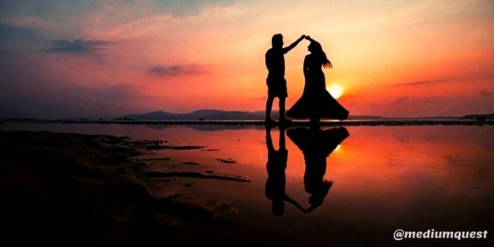 couple dancing at beach during sunset