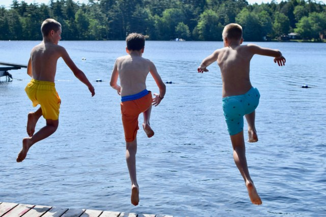 Frtiends jumping off the dock into the Lake