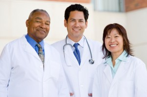 Three Doctors Standing Outside A Hospital
