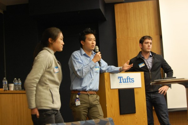 """Iris Xu (left), Steven Young (center), and Michael Tomko (right) present """"Visit-to-Visit"""" to the hackathon mentors. Photo credit: Ajay Major."""