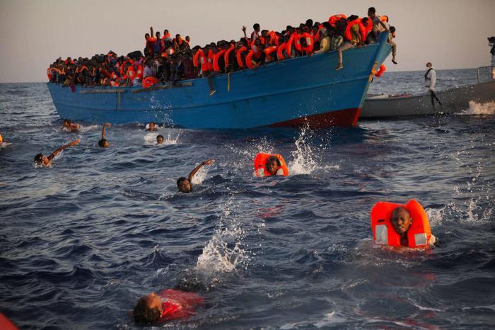 Мигранты, по большей части из Эритреи, прыгают из переполненной лодки в 13 милях от побережья Ливии, 29 августа Фото: Emilio Morenatti / AP / Scanpix / LETA