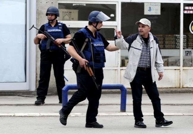 A Macedonian policeman speaks to a man near a police checkpoint in Kumanovo, Macedonia May 9, 2015. REUTERS/Ognen Teofilovski