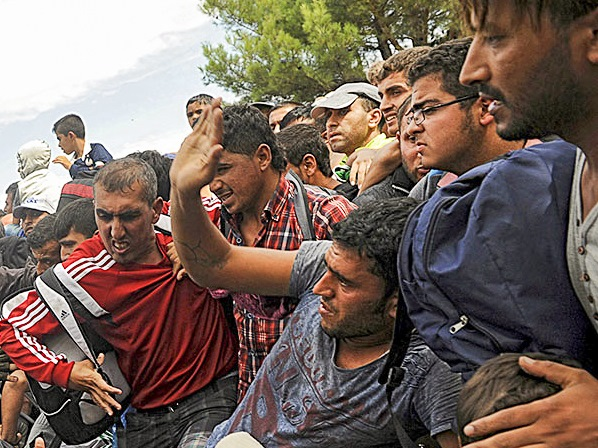 A Macedonian police officer raises his baton toward migrants to stop them from entering into Macedonia at Greece's border, near the village of Idomeni, Greece, Aug. 22, 2015.