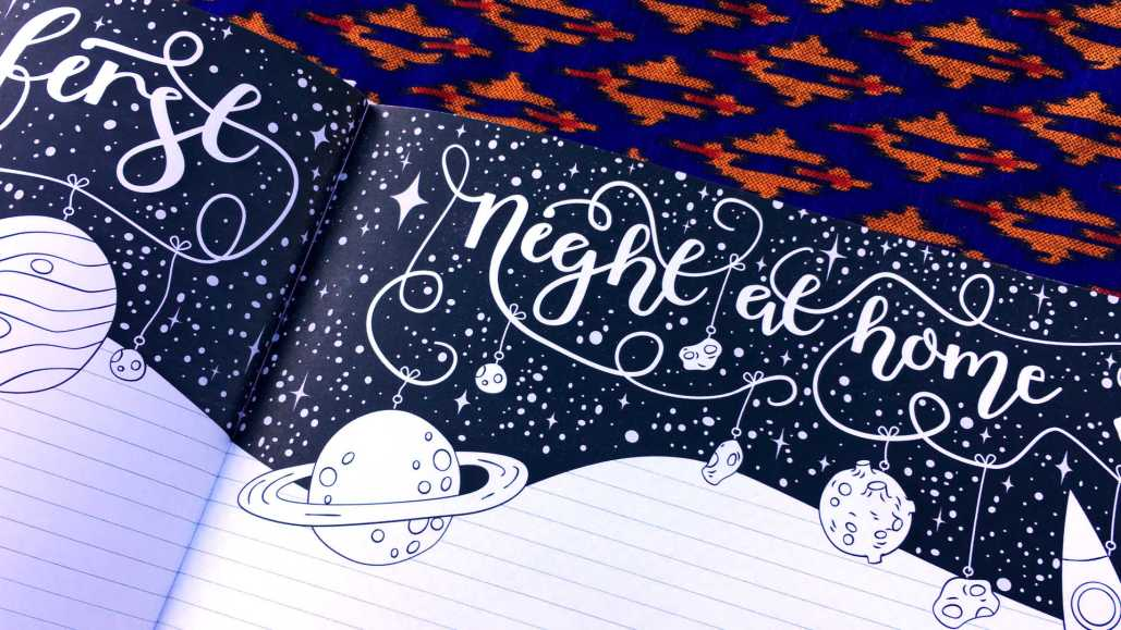 Inside page of Lilla Designs baby memory book - text reads First Night at Home accompanied by outer space illustrations.