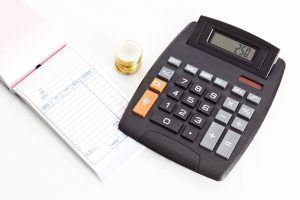 Calculator with coins and receipt book, isolated on white background