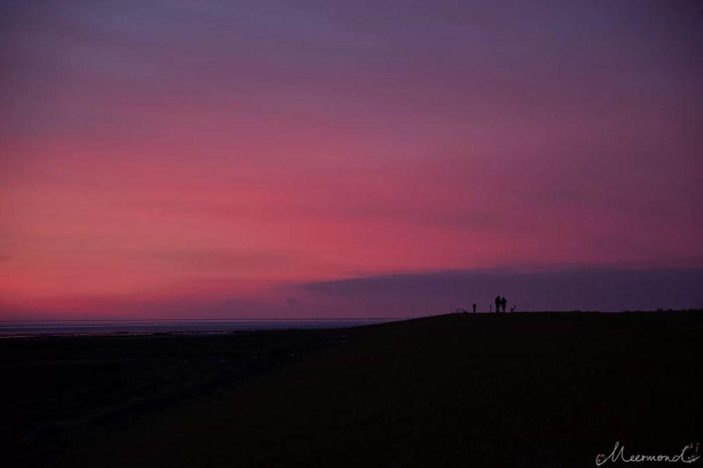 Sonnenaufgang mit Spaziergängern auf dem Deich auf Rømø