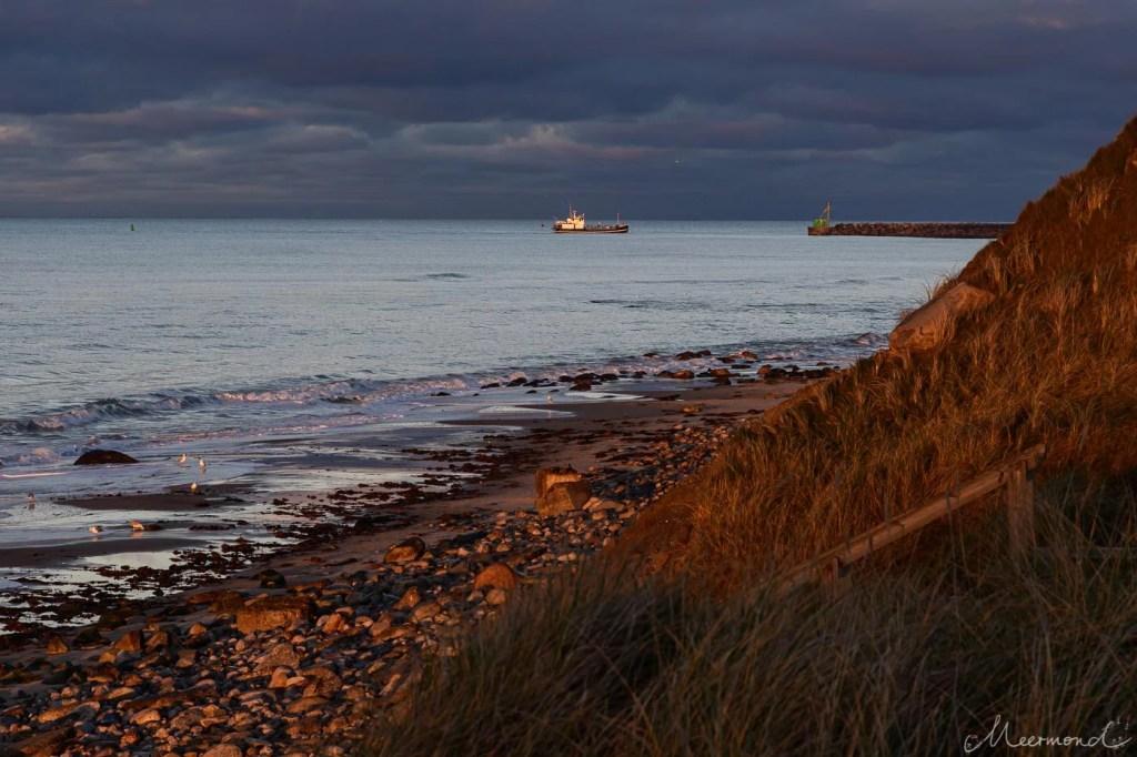 Schiff fährt in Hirtshals Hafen bei Sonnenuntergang