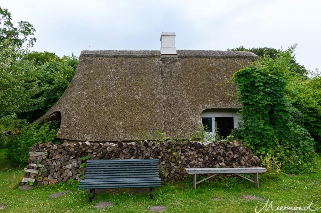 Eine Sitzbank vor aufgestapeltem Brennholz und dahinter ein Haus mit Reetdach