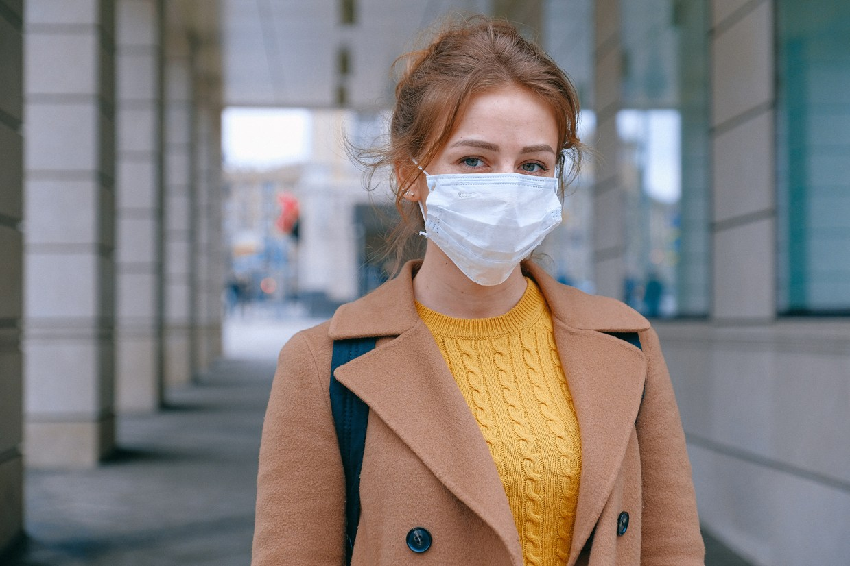 young woman wearing mask outside of building