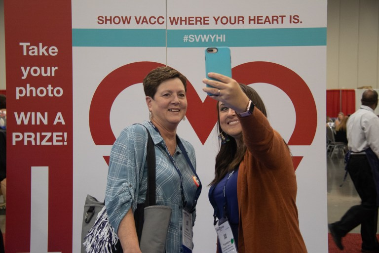 Two ladies taking a selfie in front of AVA sign