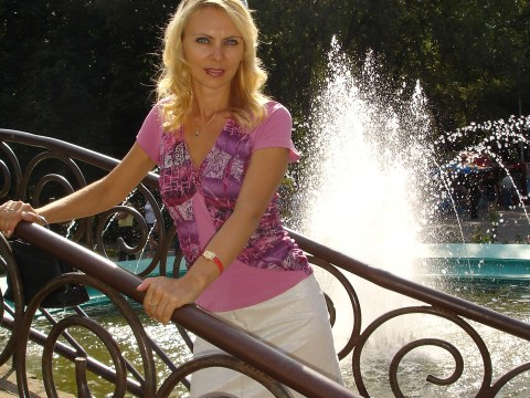 MeetLocalMILFs.Online - MILF Dating Site - Hot Blonde MILF With Beautiful Face Posing For Her Husband Near The Fountain.