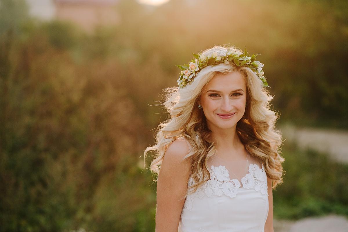 Beautiful model girl in a white wedding dress. Female portrait in the park.