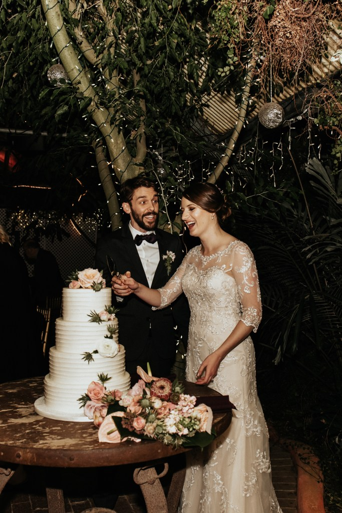 Megan Claire Photography | Arizona Wedding Photographer. Vintage inspired greenhouse arboretum wedding. Bride and groom cutting cake @meganclairephoto