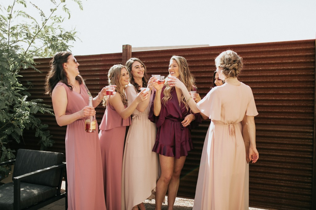 Megan Claire Photography | Arizona Wedding Photographer. Beautiful winter wedding in the desert at the Paseo in Apache Junction, Arizona near superstition mountains. Bridesmaids getting ready toasting with rosé