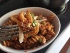 Grandma's Hamburger Rotini is shown on the end of a fork. There is Daiya cheese on the pasta